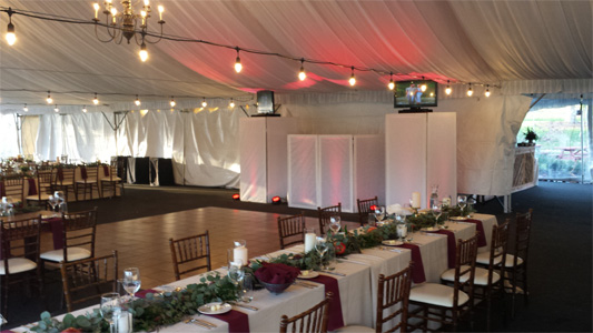 DJ Booth with white screens in tent in front of dance floor