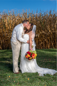 Bride & Groom kissing in front of corn field at Bittersweet Barn in New Oxford, PA