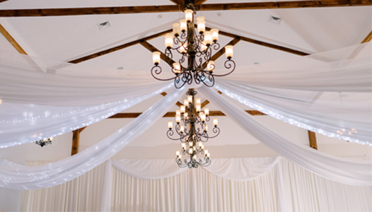 White Ceiling drapery with String lights, Pipe and Drape with Tule Accents