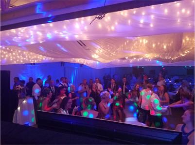 Packed Dance Floor photo taken from Wedding DJ Booth with White Drapery & Lighting above Dance Floor