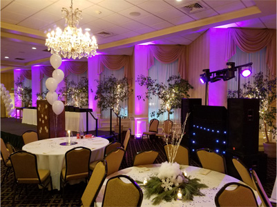 Ballroom with Purple Uplighting, round tables with white linens and DJ for Corporate Event