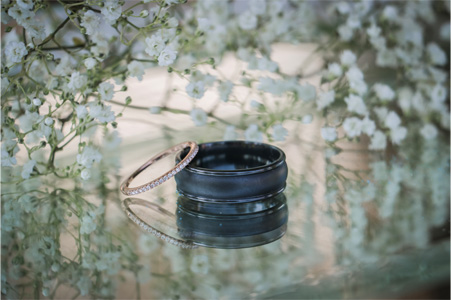 Wedding Rings on Glass Table with Baby's Breath in background